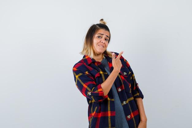 Hübsche frau in freizeitkleidung, die auf die obere rechte ecke zeigt, auf die lippe beißt und unentschlossen aussieht