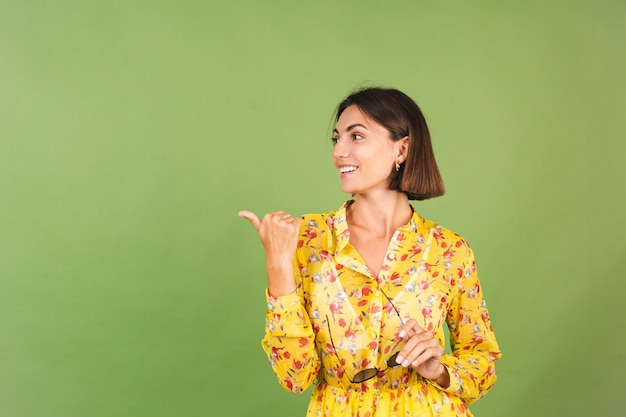 Hübsche frau in gelbem sommerkleid und sonnenbrille, grünes studio, aufgeregter fröhlicher, fröhlicher zeigefinger links