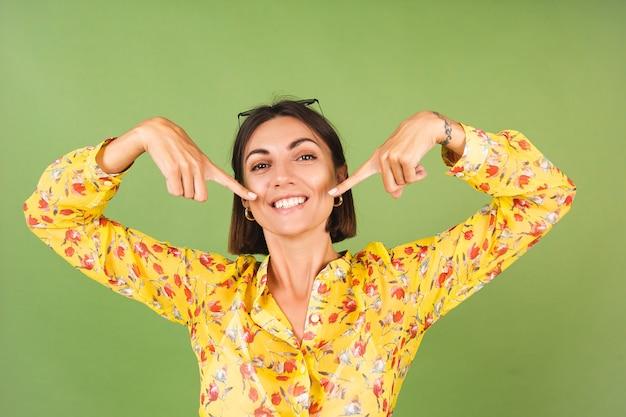 Hübsche frau in gelbem sommerkleid und sonnenbrille, grünes studio, aufgeregter fröhlicher zeigefinger auf perfekten weißen zähnen
