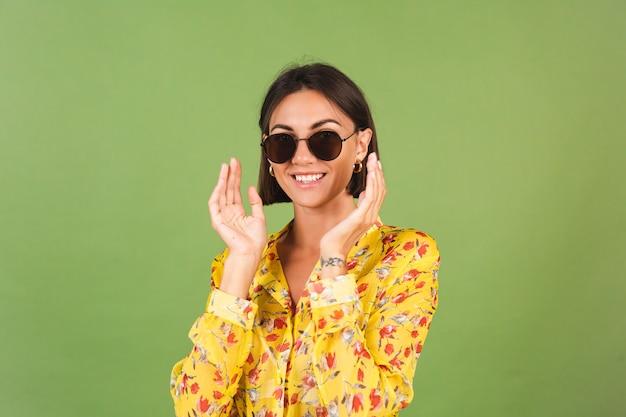 Hübsche frau in gelbem sommerkleid und sonnenbrille, grünes studio, glückliche positive fröhliche freudige emotionen