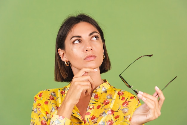 Hübsche frau in gelbem sommerkleid und sonnenbrille, grünes studio, nachdenklicher blick beiseite