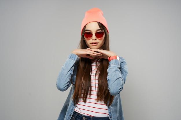 Hübsche frau in jeanshemd sonnenbrille rosa hut posiert mode grauen hintergrund studio Premium Fotos