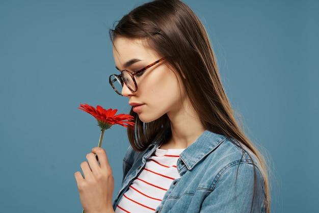 Hübsche frau in jeansjacke rote blumenbrille mode
