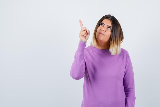 Hübsche frau in lila pullover, die auf die obere linke ecke zeigt und fokussiert aussieht, vorderansicht.