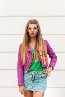 Hübsche frau in modischer sonnenbrille und einer rosa jacke