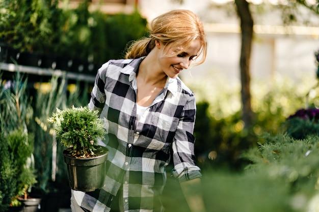 Hübsche frau in niedlichen kleidern, die nach pflanzen im gewächshaus greifen