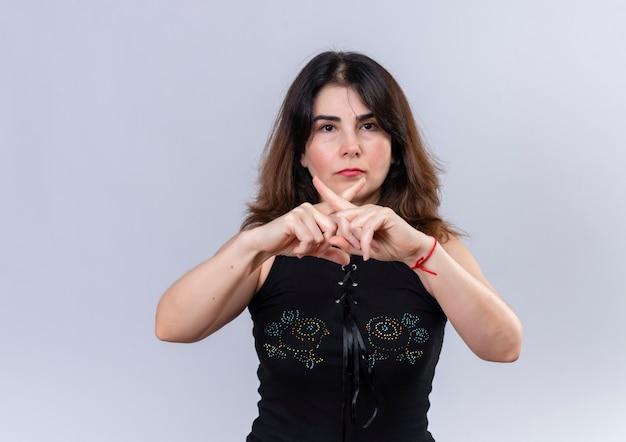 Hübsche frau in schwarzen blusen, die verbot mit ihren fingern zeigt