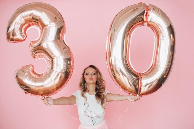 Hübsche frau in sommerkleidung hat viel spaß gemacht und feiert ihren geburtstag, bild einzeln auf rosa hintergrund