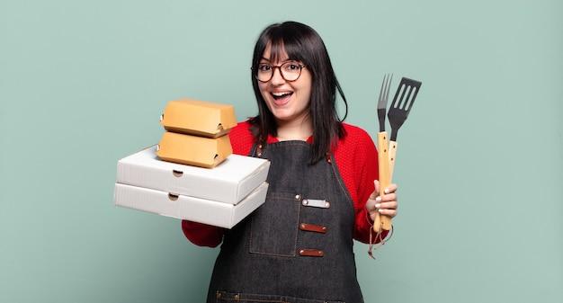 Hübsche frau in übergröße liefert kochen, fast-food-konzept zum mitnehmen