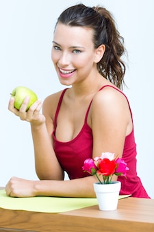 Hübsche frau isst einen grünen apfel