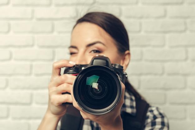 Hübsche frau ist ein professioneller fotograf mit dslr-kamera