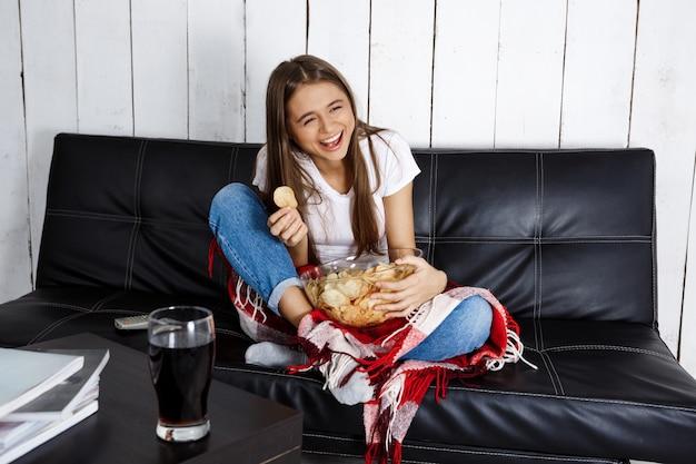 Hübsche frau lacht, sieht fern und sitzt zu hause auf dem sofa.