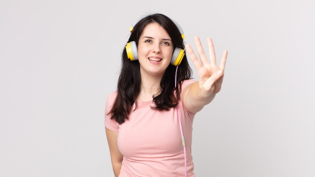 Hübsche frau lächelt und sieht freundlich aus und zeigt nummer vier, die musik mit kopfhörern hört