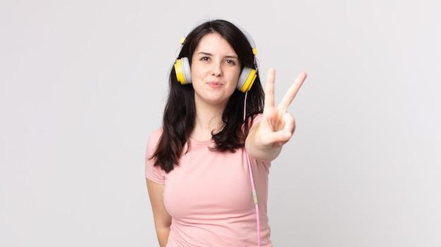 Hübsche frau lächelt und sieht freundlich aus und zeigt nummer zwei, die musik mit kopfhörern hört
