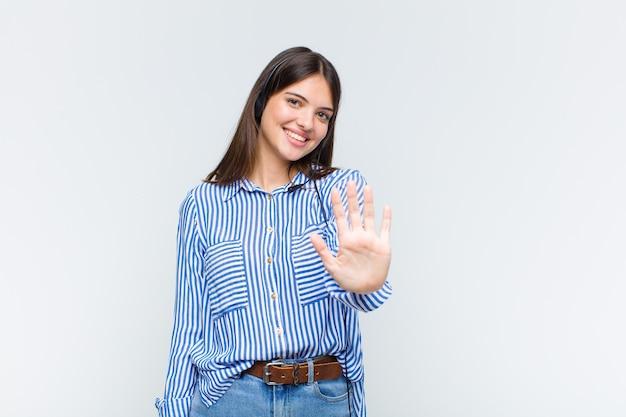 Hübsche frau lächelt und sieht freundlich aus, zeigt nummer fünf oder fünfte mit der hand nach vorne und zählt herunter