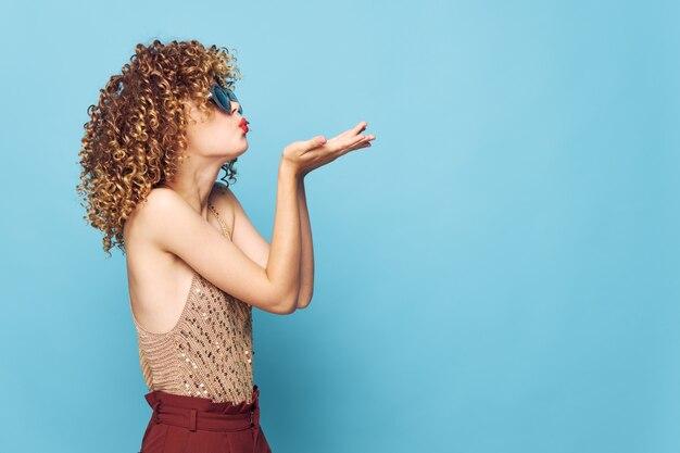 Hübsche frau luftkussgesten für lockiges haar mit blauen händen