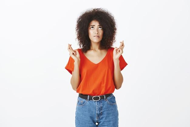 Hübsche frau mit afro-frisur, die im studio aufwirft