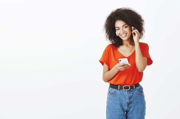Hübsche frau mit afro-frisur, die mit ihrem smartphone und ohrhörern im studio aufwirft