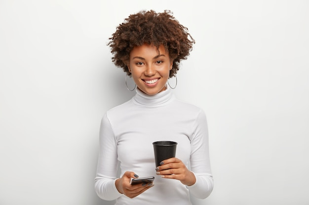 Hübsche frau mit afro-frisur, hält modernes handy und kaffee zum mitnehmen, verbringt freizeit mit online-chats