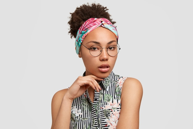 Hübsche frau mit afro-frisur, schaut ernst und geheimnisvoll in die kamera, fühlt sich selbstsicher oder selbstbewusst