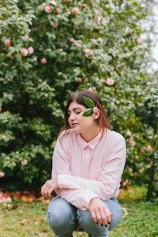 Hübsche frau mit anlage im haar nahe den rosa blumen, die auf grünen zweigen wachsen