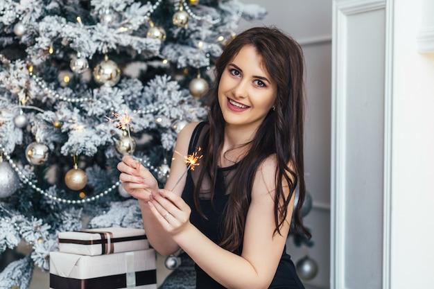 Hübsche frau mit bengal-feuern lächelt die aufstellung vor dem weihnachtsbaum, der mit schnee bedeckt wird