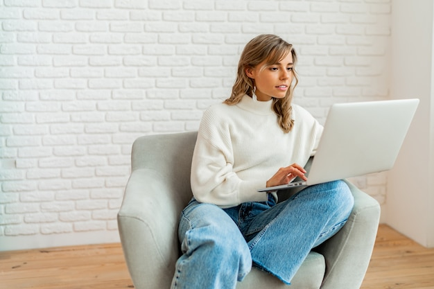 Hübsche frau mit blonden, gewellten haaren, die zu hause auf dem sofa sitzt und an einem laptop arbeitet