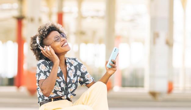 Hübsche frau mit blonden haaren und brille, mit freizeitkleidung, hört musik mit ihrem smartphone auf der straße