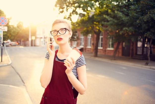 Hübsche frau mit brille auf der straße, die im sommer telefoniert