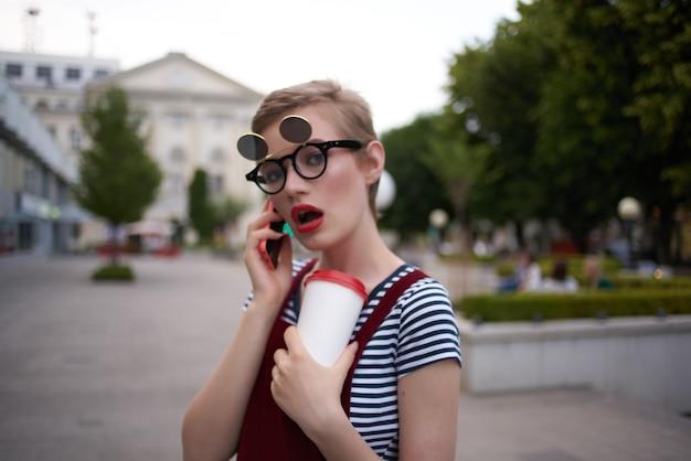 Hübsche frau mit brille, die über den lebensstil der straße telefoniert