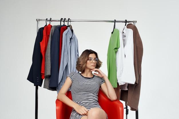 Hübsche frau mit brillenauswahl an kleidung in der nähe des garderobenstudio-lifestyles