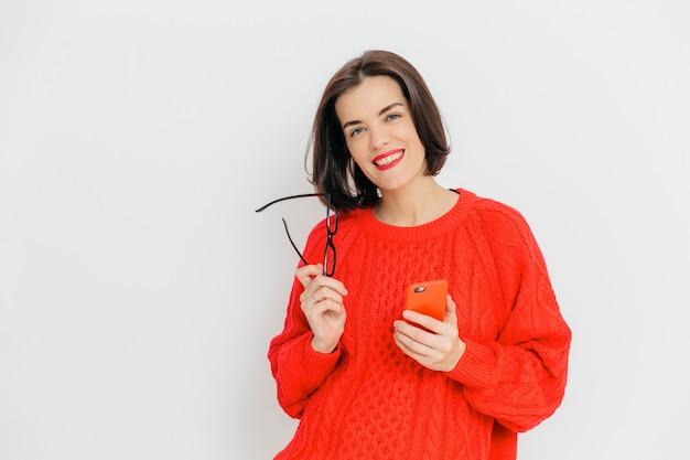 Hübsche frau mit dem dunklen kurzen haar, trägt übergroße rote winterstrickjacke, hält eyewear und intelligentes telefon