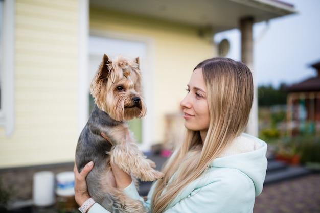Hübsche frau mit dem langen blonden haar, das hundyorkshire-terrier im freien hält