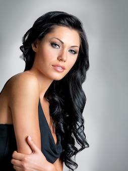 Hübsche frau mit dem langen braunen haar der schönheit, das im studio auf grauem hintergrund aufwirft