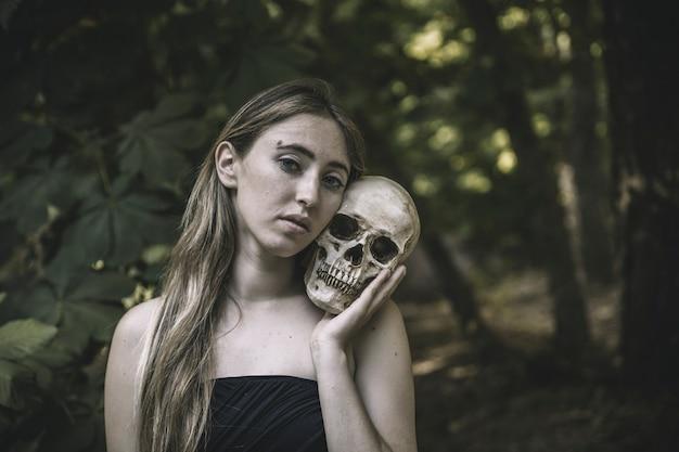 Hübsche frau mit dem menschlichen schädel in der dickichtstageszeit