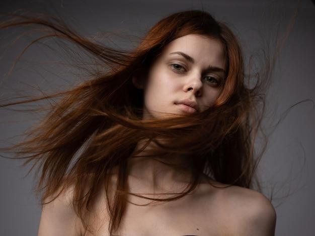 Hübsche frau mit den roten haaren auf einer grauen hintergrundnackte schultern unten ansicht