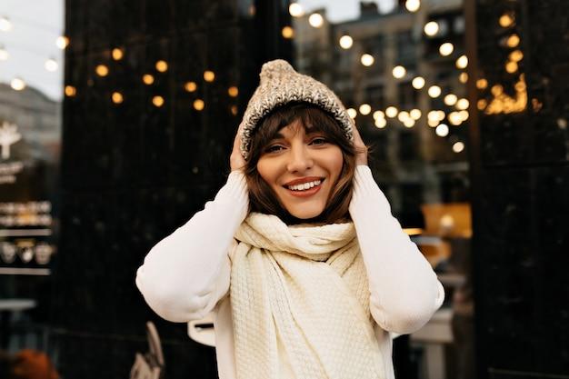 Hübsche frau mit dunklem haar, das spaß außerhalb des modernen niedlichen weiblichen getränks hat, das weihnachten auf stadthintergrund vorbereitet hochqualitätsfoto