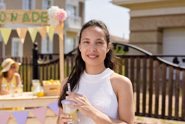 Hübsche frau mit dunklem langem haar mit einem glas frischer kühler hausgemachter limonade, die sie an einem heißen sommertag am stand in der nähe gekauft hat