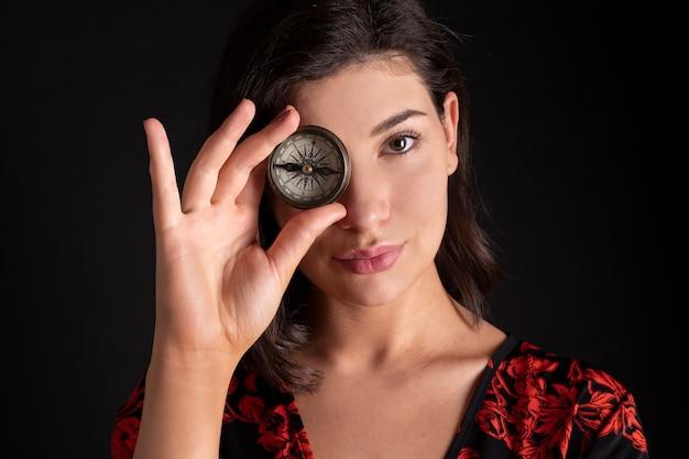Hübsche frau mit einem kompass, der ihr auge bedeckt