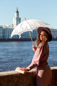 Hübsche frau mit einem regenschirm von der sonne