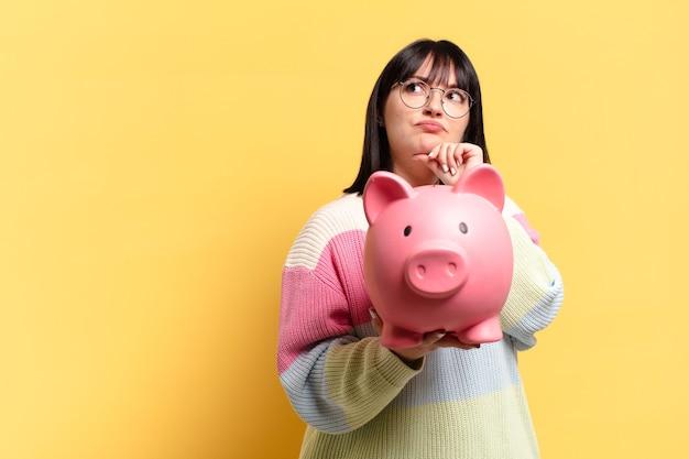 Hübsche frau mit einem sparschwein