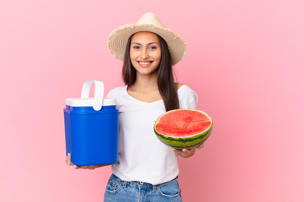 Hübsche frau mit einem tragbaren gefrierschrank und einer wassermelone