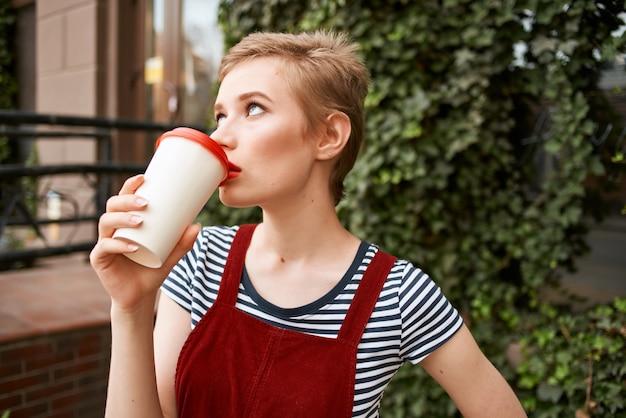 Hübsche frau mit einer tasse kaffee spaziergang im freien freizeit