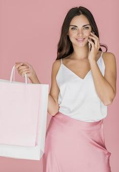 Hübsche frau mit einkaufsnetzen und smartphone