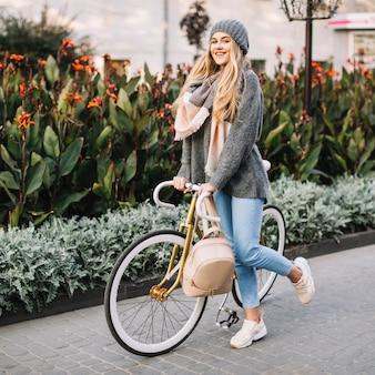 Hübsche frau mit fahrrad nahe blumenbeet