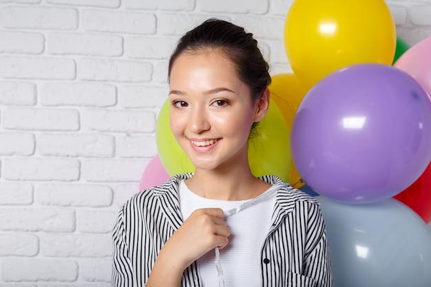 Hübsche frau mit farbigen ballonen