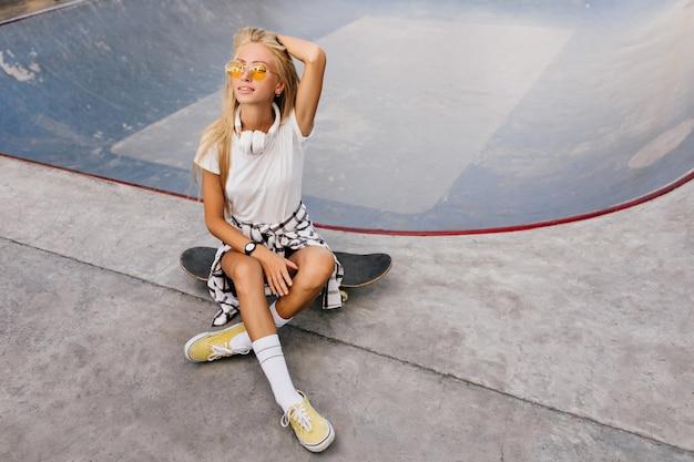 Hübsche frau mit gebräunter haut, die auf skateboard sitzt und mit blonden haaren spielt.