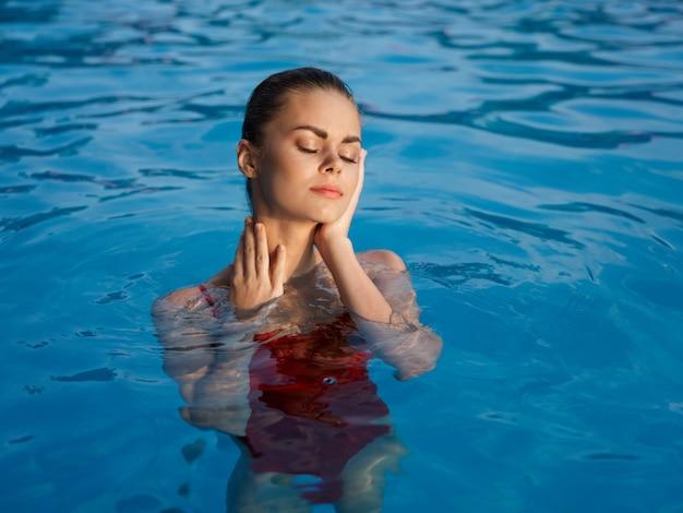 Hübsche frau mit geschlossenen augen glamour und rotem luxusbadeanzug
