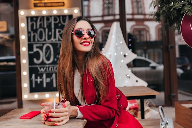 Hübsche frau mit glänzendem braunem haar, das am wochenende im café kühlt
