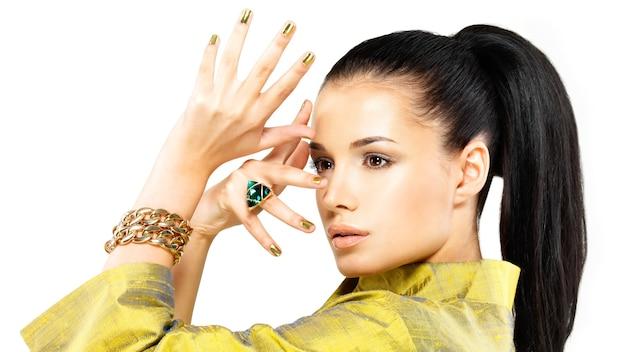 Hübsche frau mit goldenen nägeln und schönem edelstein-smaragd - lokalisiert auf weißem hintergrund